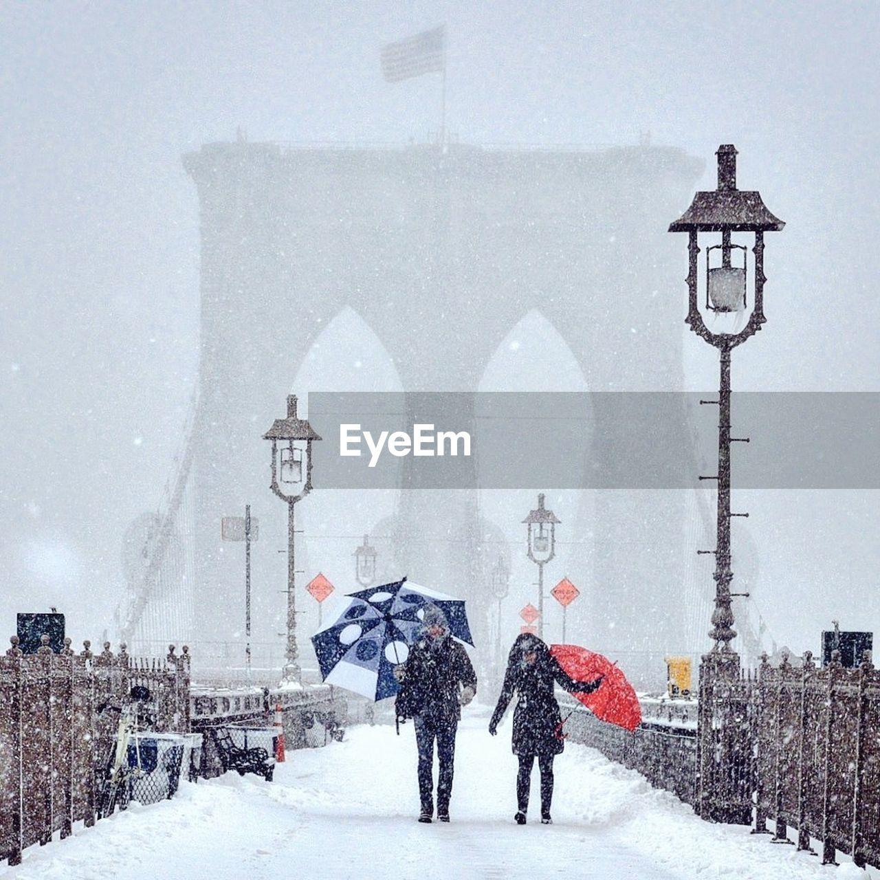Man and woman walking at brooklyn bridge during snowfall