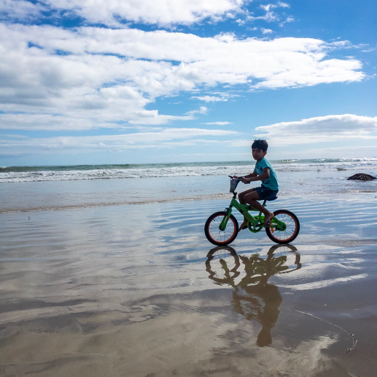 Side view of boy riding bicycle on shore at beach against sky