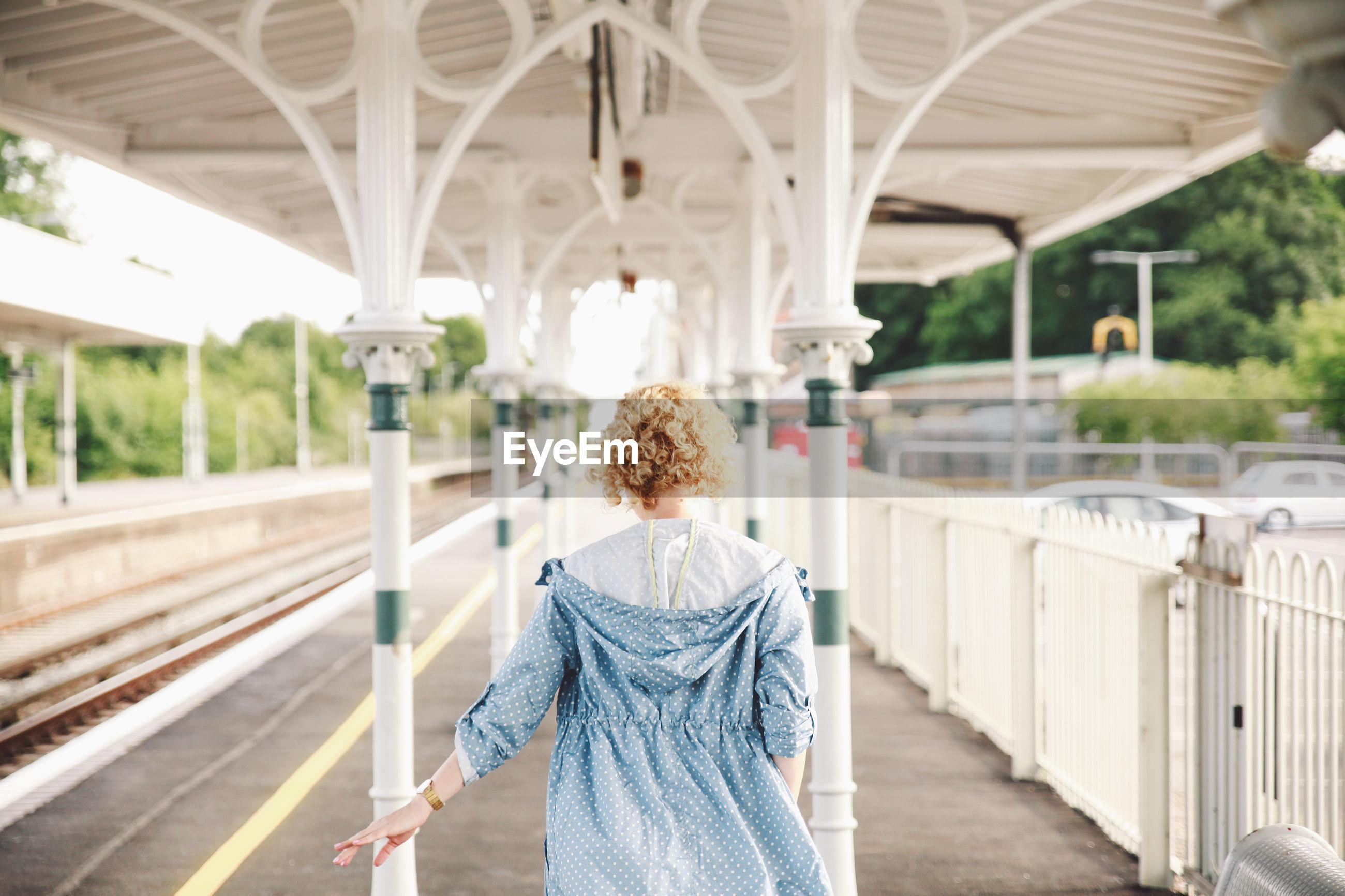 Rear view of woman walking at railroad station platform