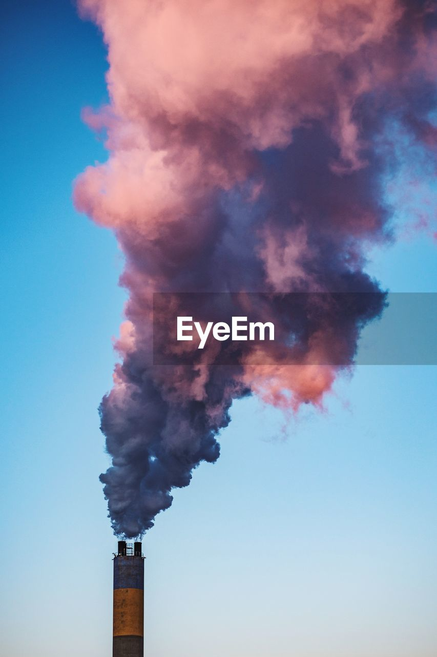 smoke - physical structure, factory, building exterior, pollution, environmental issues, sky, smoke stack, air pollution, industry, architecture, built structure, no people, emitting, nature, environment, social issues, environmental damage, day, low angle view, chimney, outdoors, fumes, smog, ecosystem