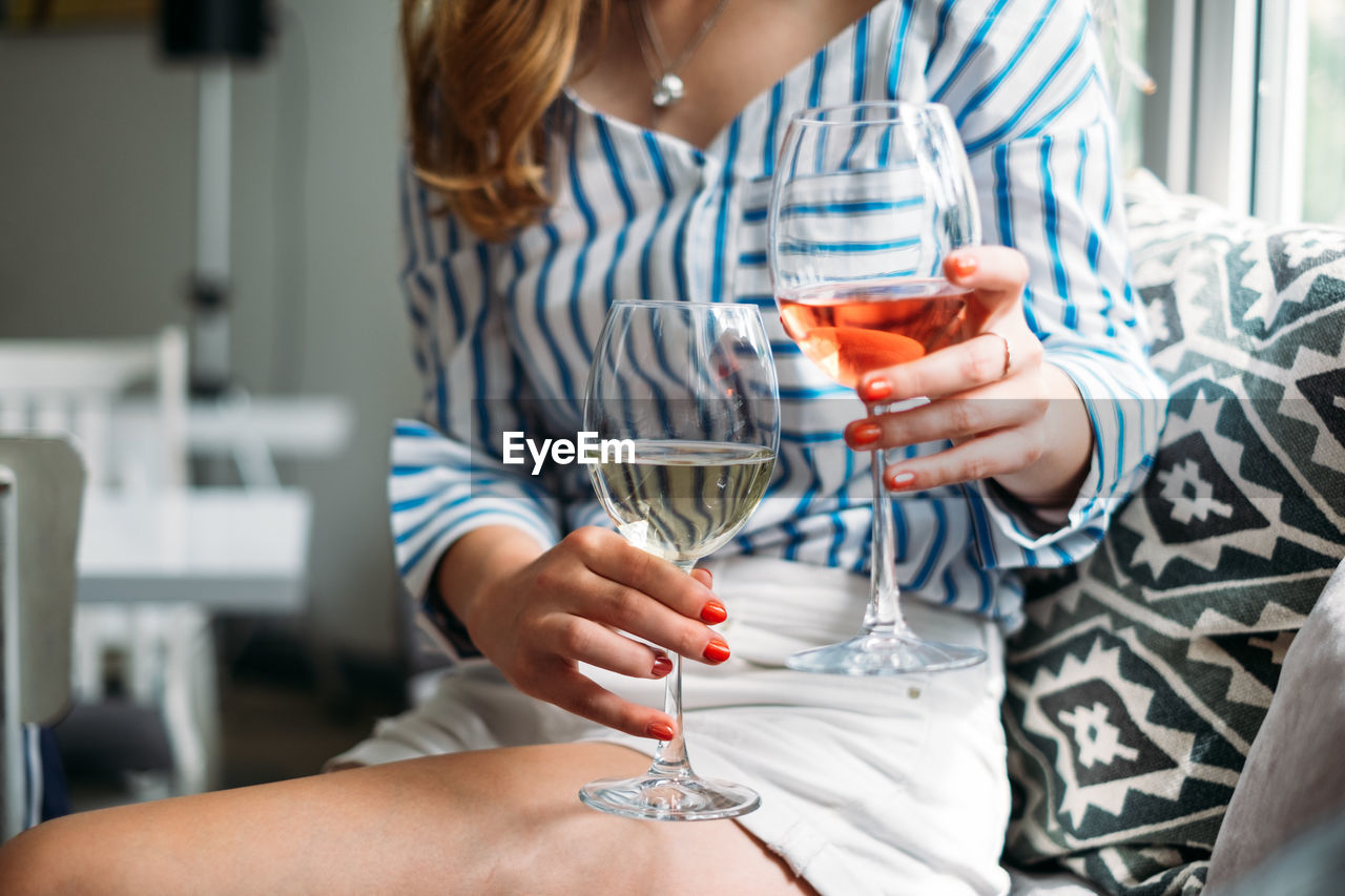 Midsection Of Woman Holding Wineglasses While Sitting On Sofa