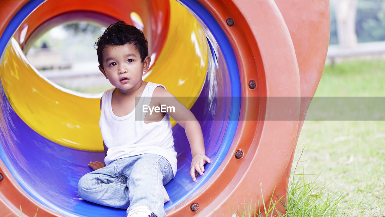 childhood, child, one person, innocence, real people, playground, males, boys, leisure activity, playing, cute, lifestyles, casual clothing, men, full length, front view, outdoor play equipment, slide - play equipment, outdoors, jungle gym