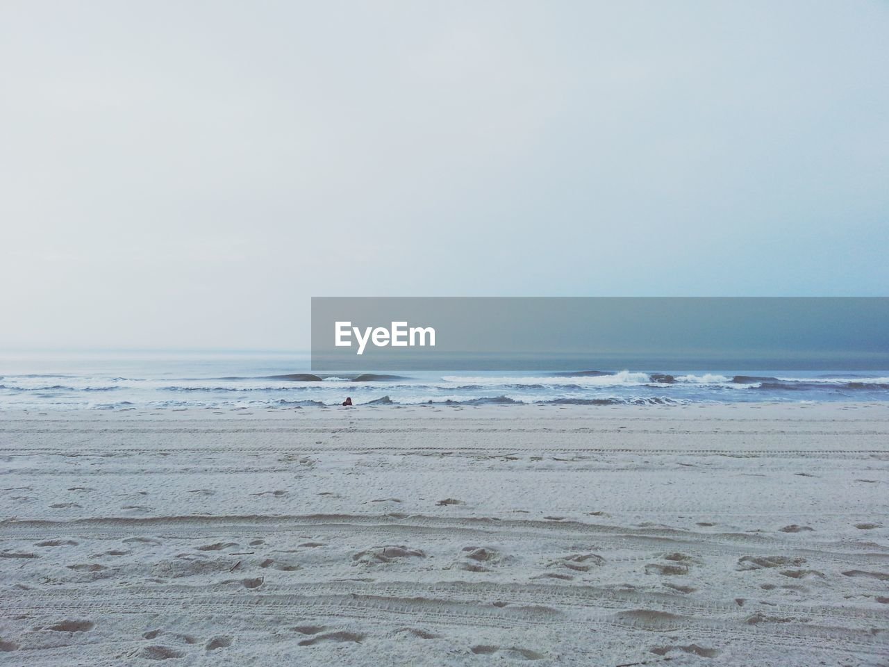 Scenic view of calm beach and crashing waves against clear sky