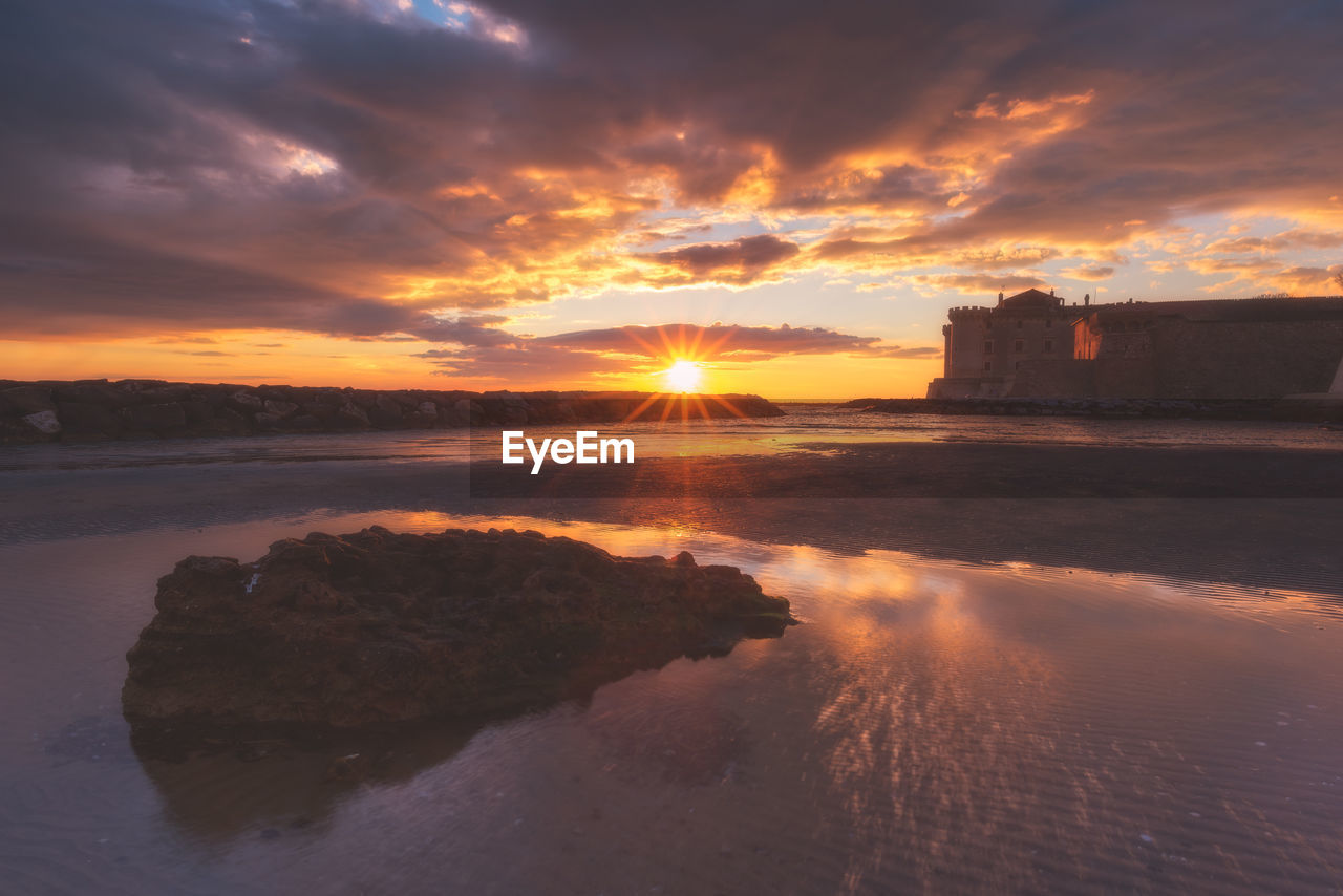 sunset, sun, sky, sea, orange color, cloud - sky, water, architecture, reflection, sunlight, scenics, beauty in nature, nature, built structure, no people, building exterior, outdoors, day
