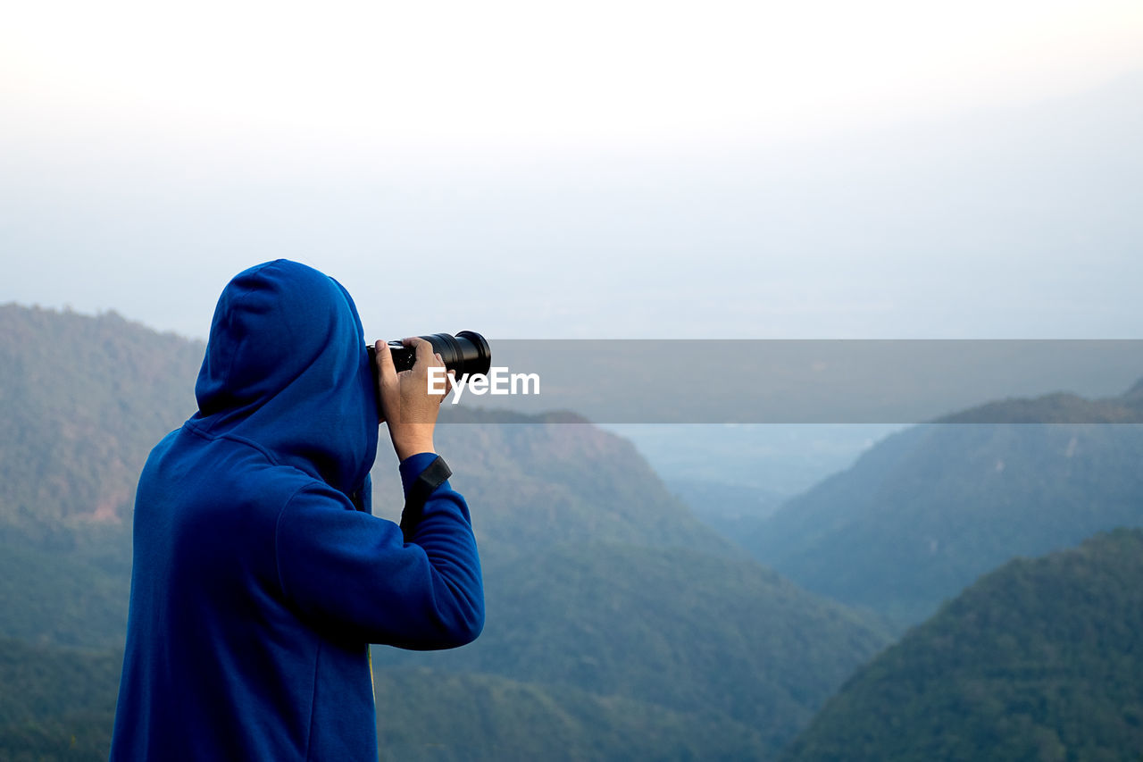 Rear view of person photographing mountains from camera