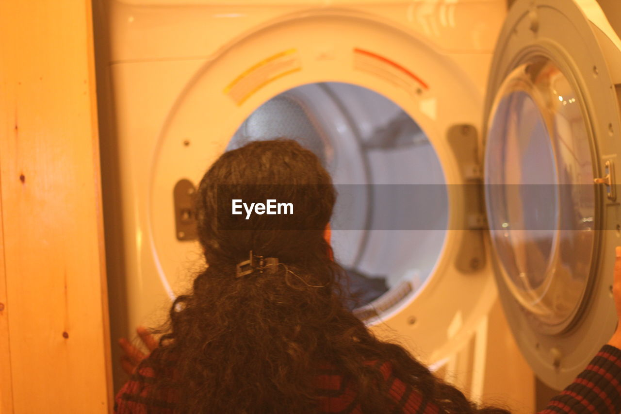 Rear view of woman opening laundromat door