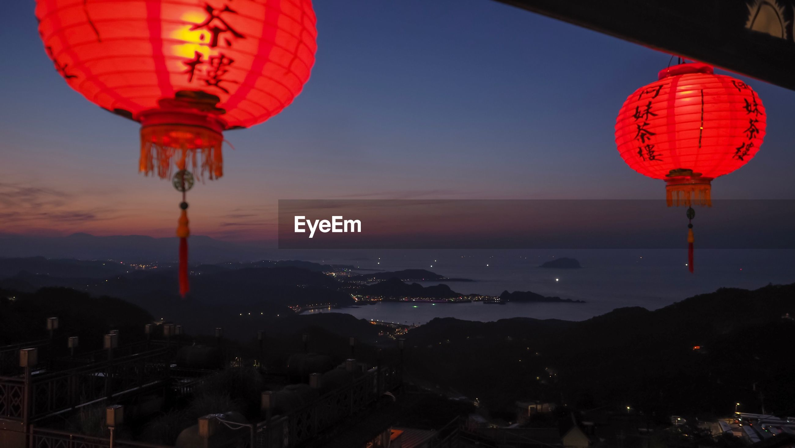 LOW ANGLE VIEW OF ILLUMINATED LANTERNS HANGING AGAINST SKY DURING SUNSET