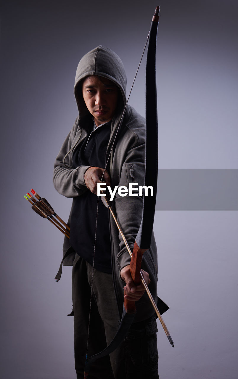Mature Man With Bow And Arrow Standing Against Gray Background