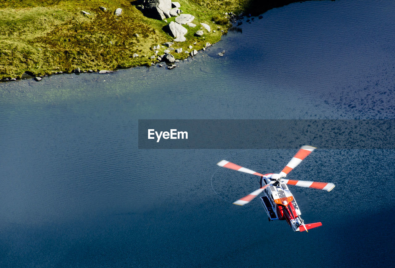 High Angle View Of Rescue Helicopter Flying Over Lake At Snowdonia National Park