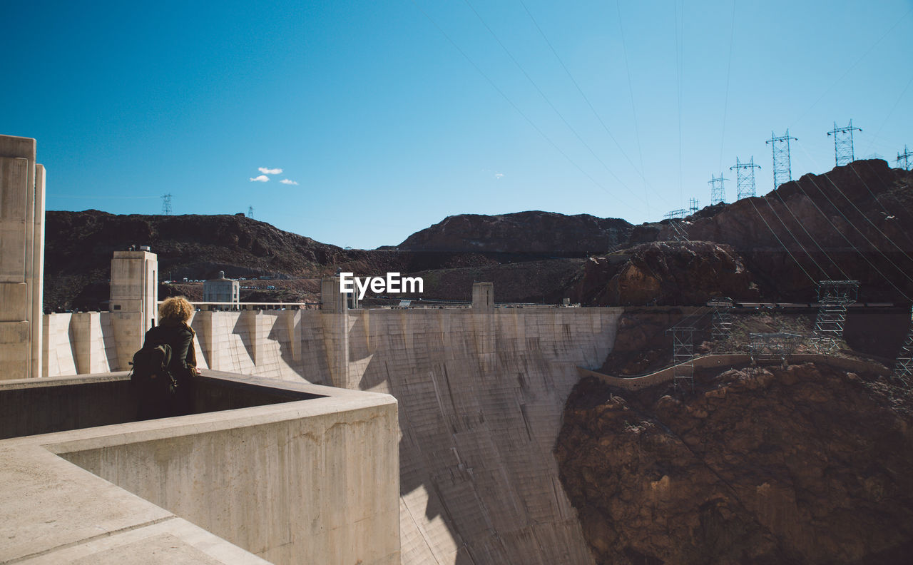 Rear View Of Woman Looking At Hoover Dam Against Sky During Sunny Day