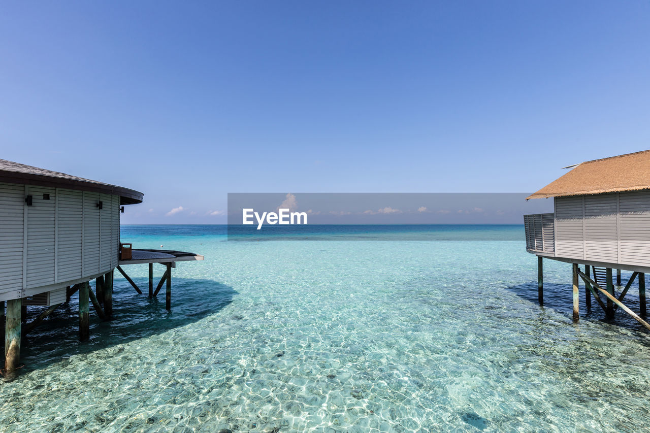 water, sky, sea, architecture, built structure, scenics - nature, beauty in nature, horizon, horizon over water, blue, beach, nature, tranquil scene, tranquility, land, day, hut, copy space, building exterior, no people, outdoors, turquoise colored