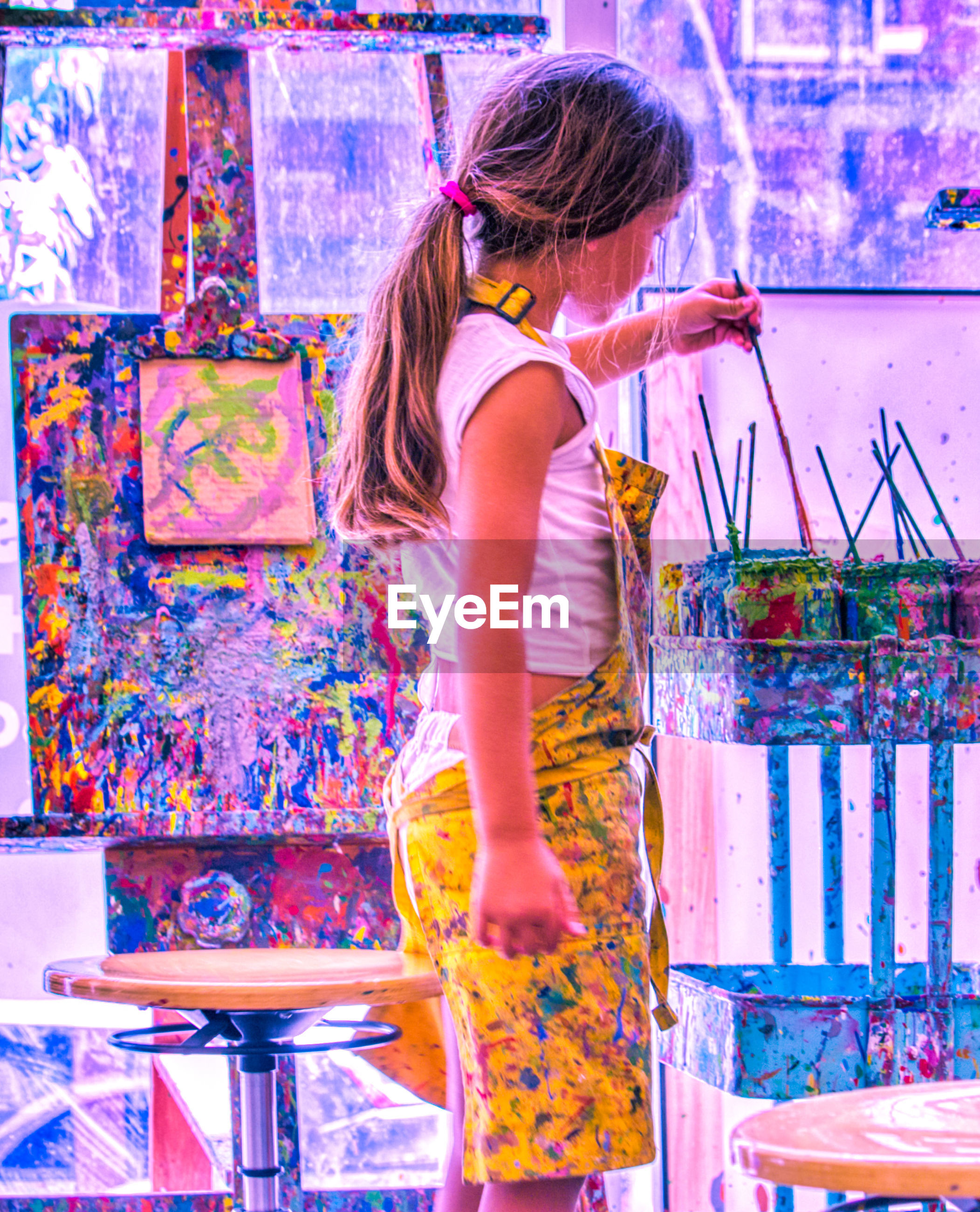 Side view of girl painting in art studio