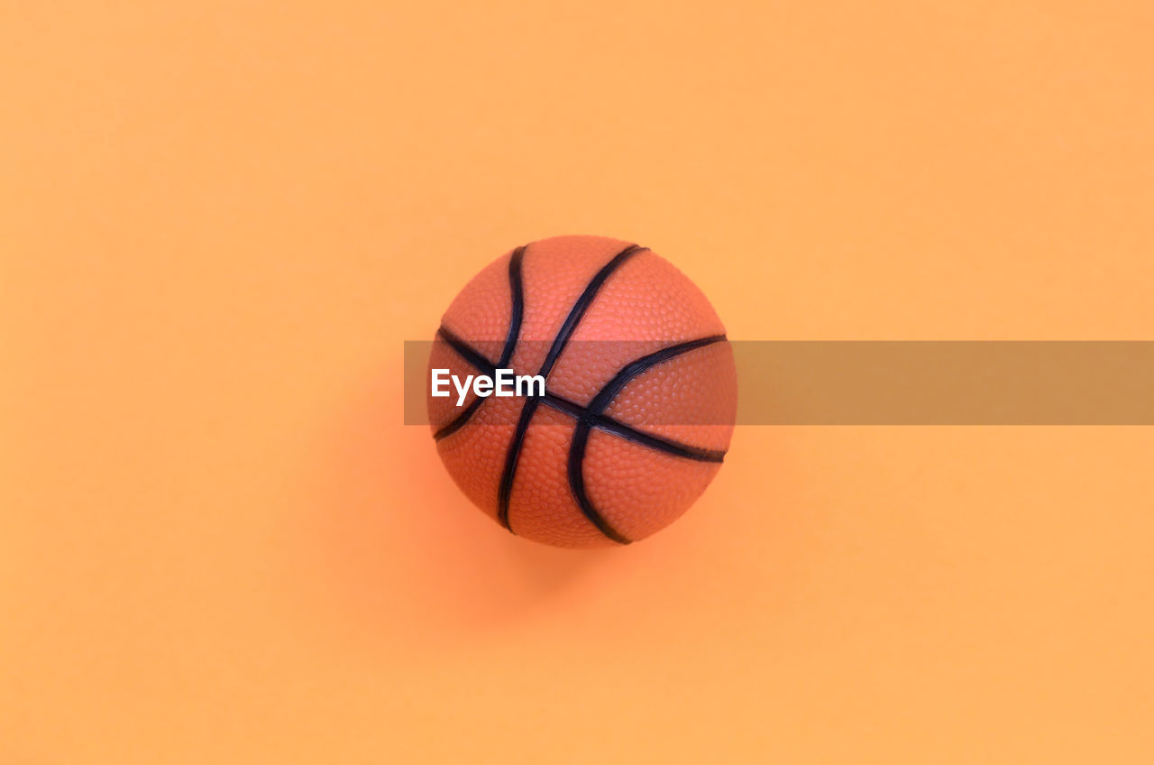 ball, orange color, sport, basketball - sport, studio shot, indoors, copy space, single object, colored background, sports equipment, basketball - ball, close-up, no people, court, sphere, still life, motion, shape, team sport, red, orange background