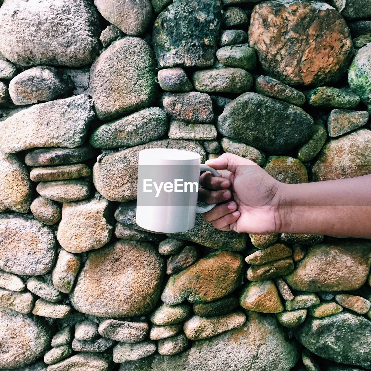 human body part, human hand, hand, one person, real people, drink, holding, cup, refreshment, coffee, mug, coffee - drink, food and drink, stone - object, coffee cup, solid, lifestyles, body part, wall, finger, stone wall, human limb, non-alcoholic beverage