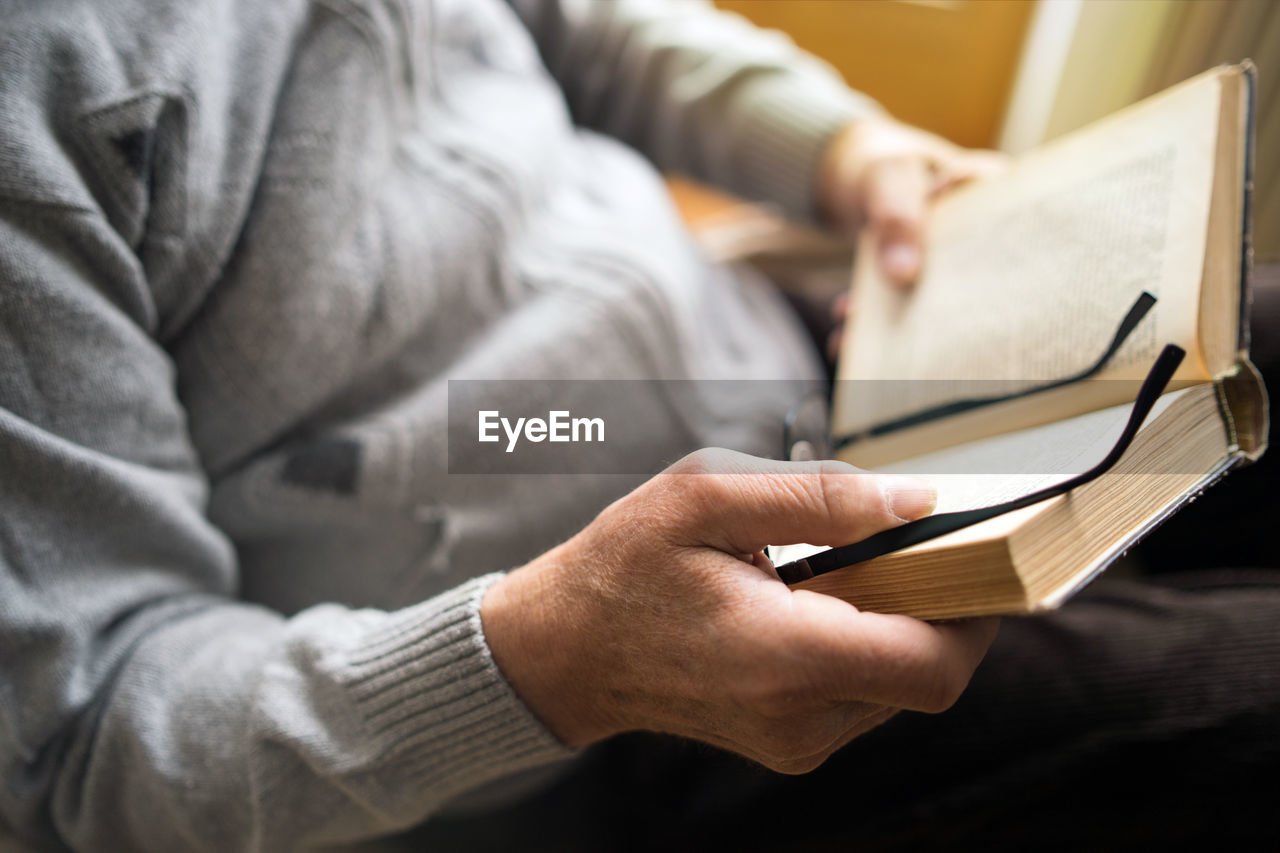 Midsection Of Man Holding Book And Eyeglasses At Home