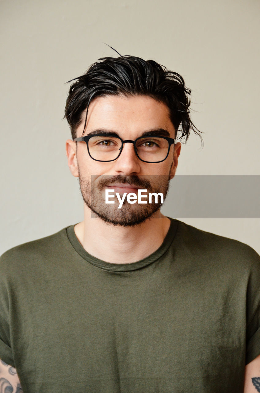 eyeglasses, glasses, front view, portrait, looking at camera, one person, indoors, beard, young adult, casual clothing, headshot, studio shot, facial hair, young men, waist up, confidence, adult, t-shirt, hairstyle, contemplation