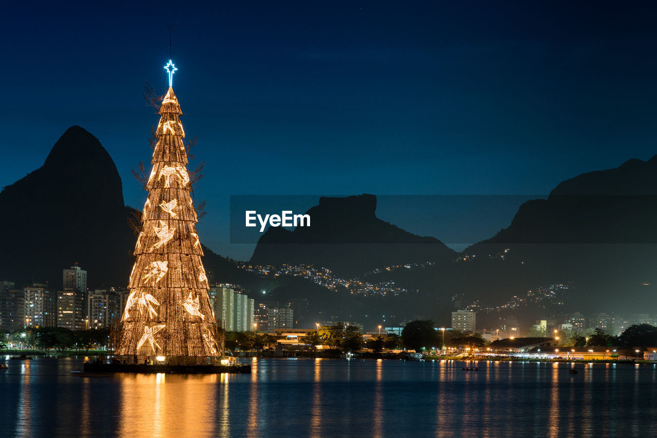 Illuminated Artificial Christmas Tree In City Against Sky At Night