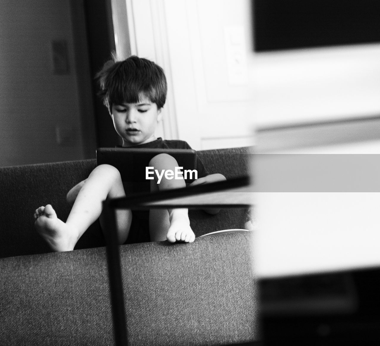 Full length of boy sitting with digital tablet on sofa at home