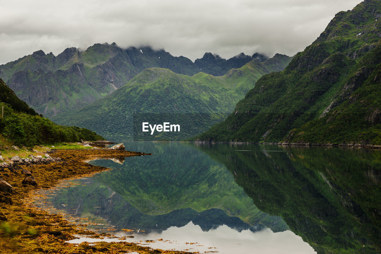 Scenic View Of Green Mountains Reflecting On Lake