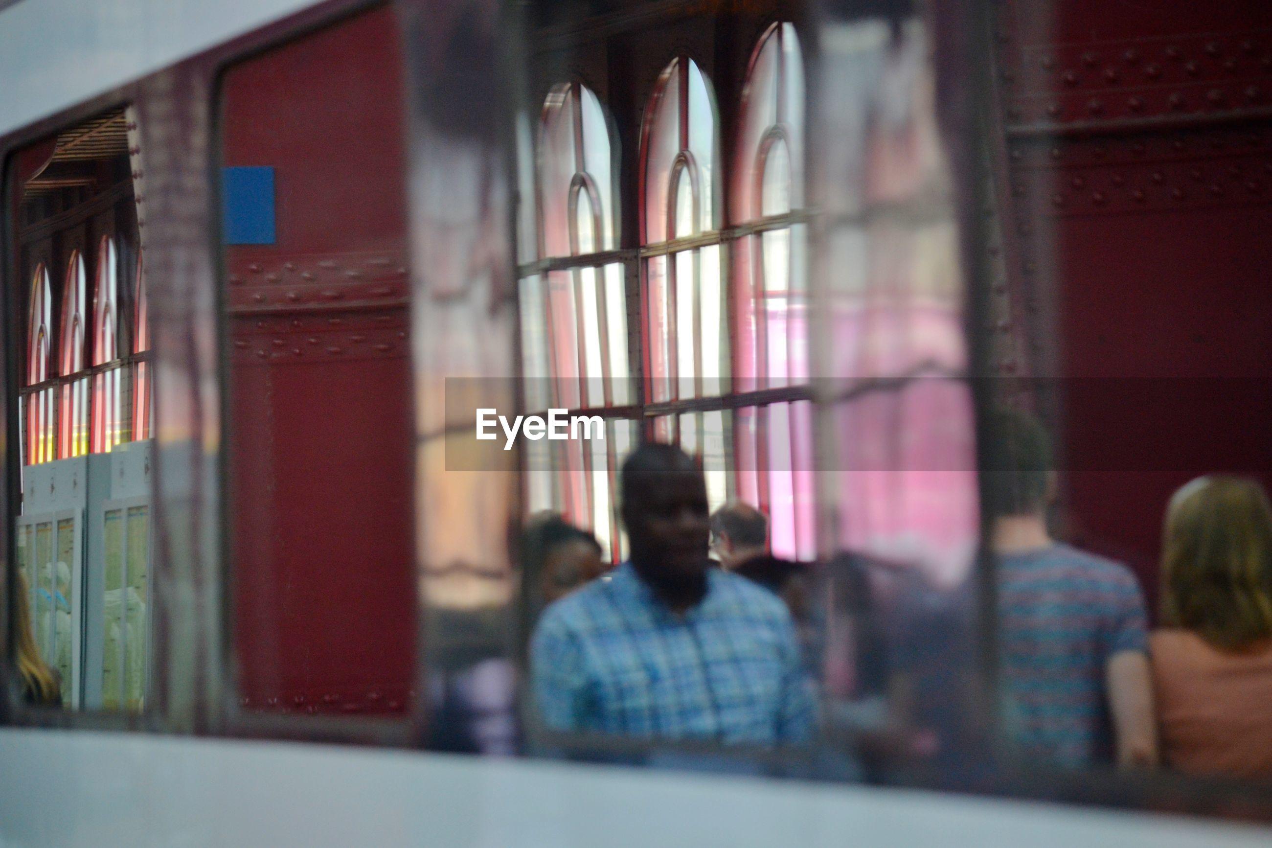 People walking in corridor seen through window