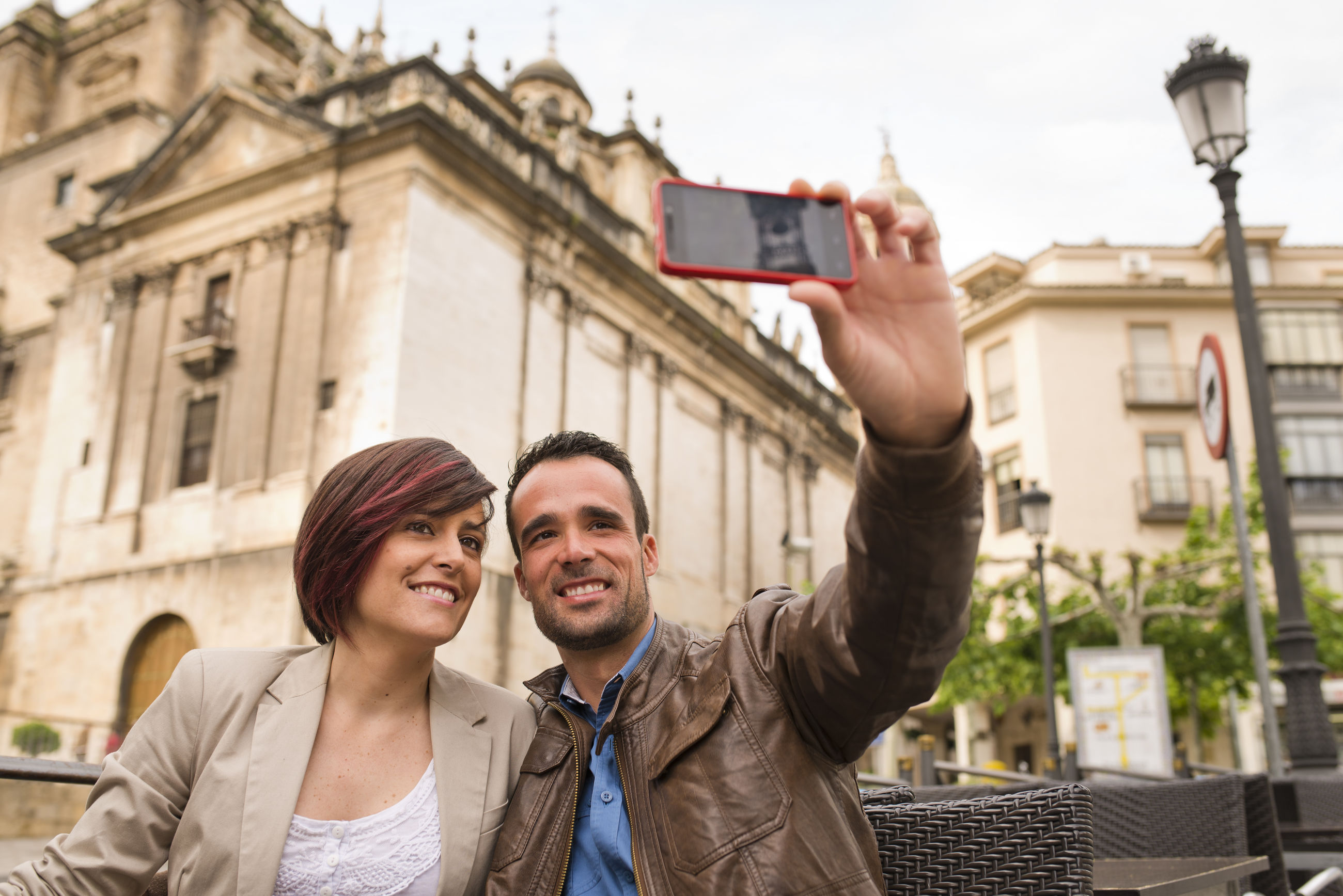 Couple taking selfie through mobile phones in city