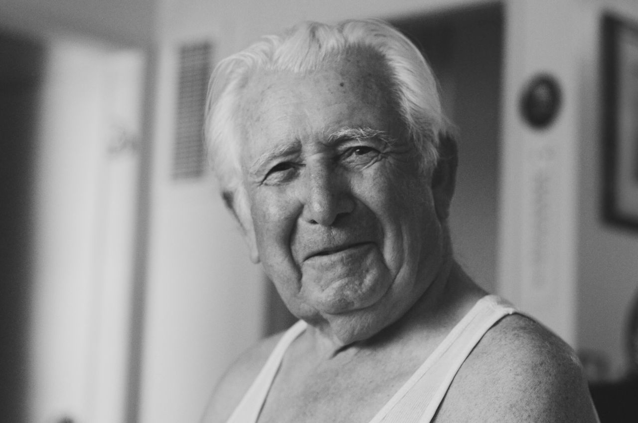 Close-Up Portrait Of Senior Man Sitting At Home