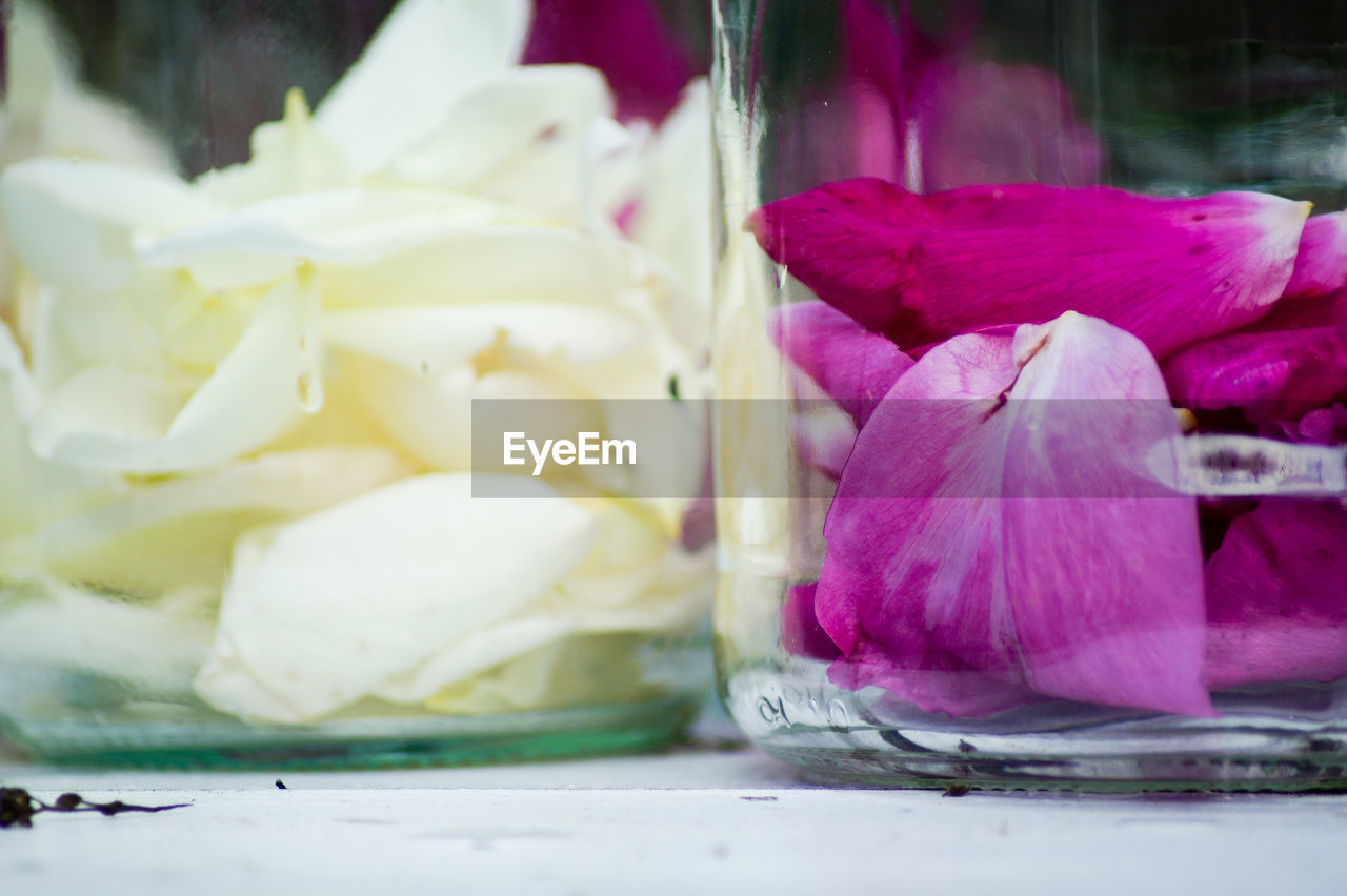 Close-Up Of Rose Petals In Glass Jars On Table