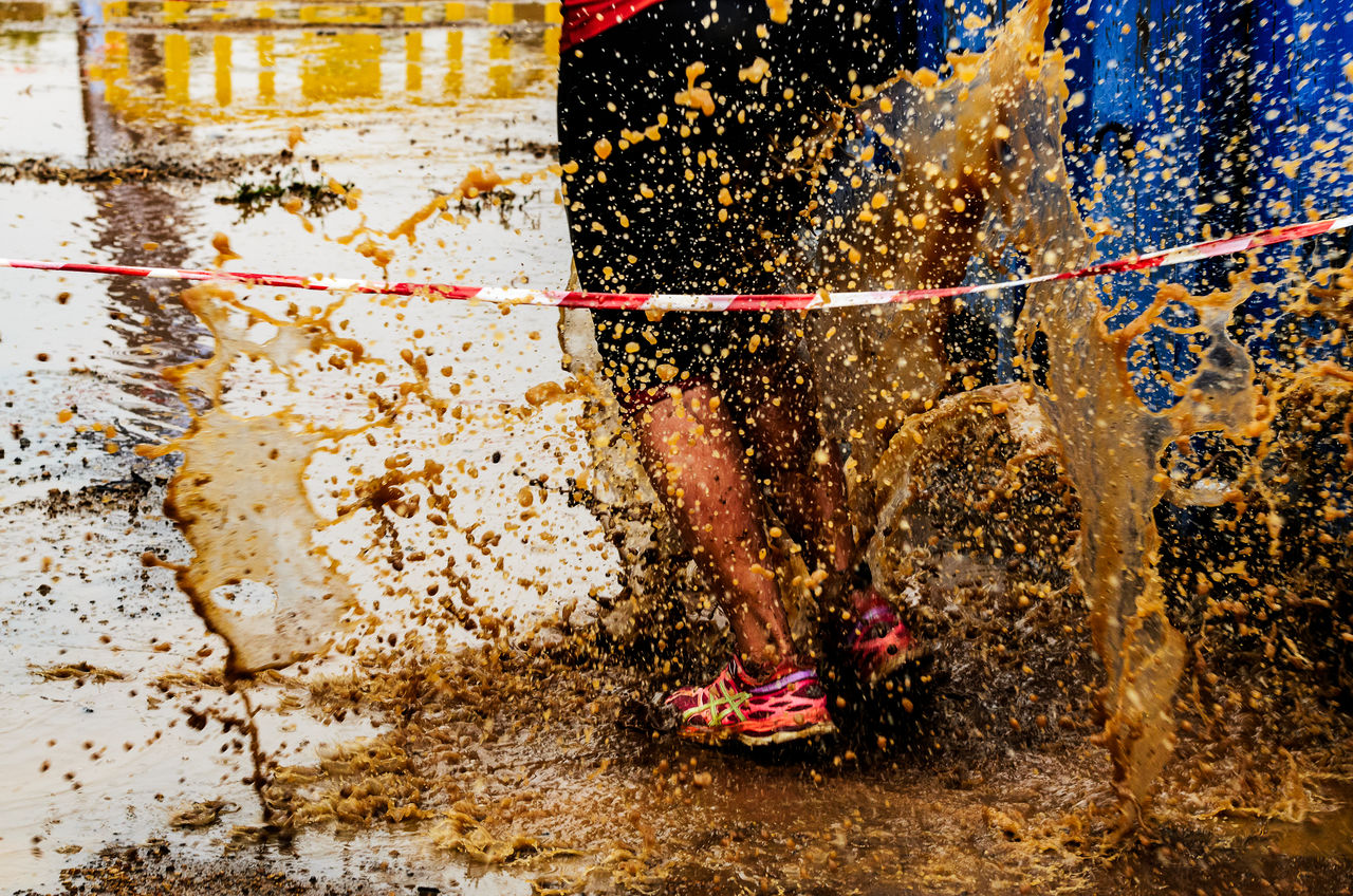 Low Section Of Person Splashing Mud In Puddle On Road