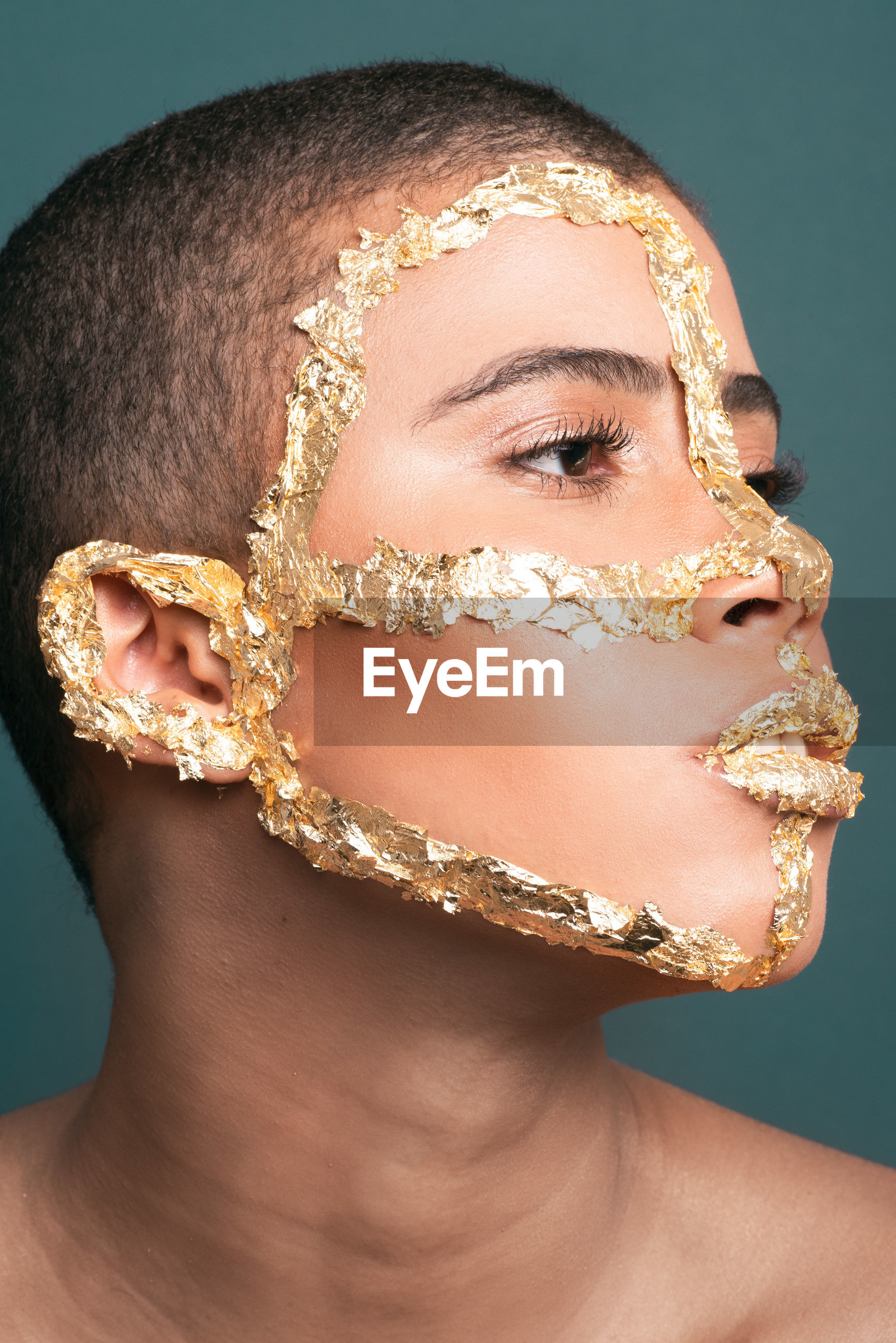 Close-up woman with golden make-up foil on face against blue background