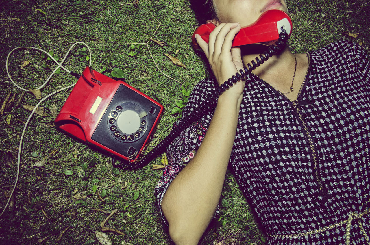 High Angle View Of Young Woman Using Telephone On Grassy Field