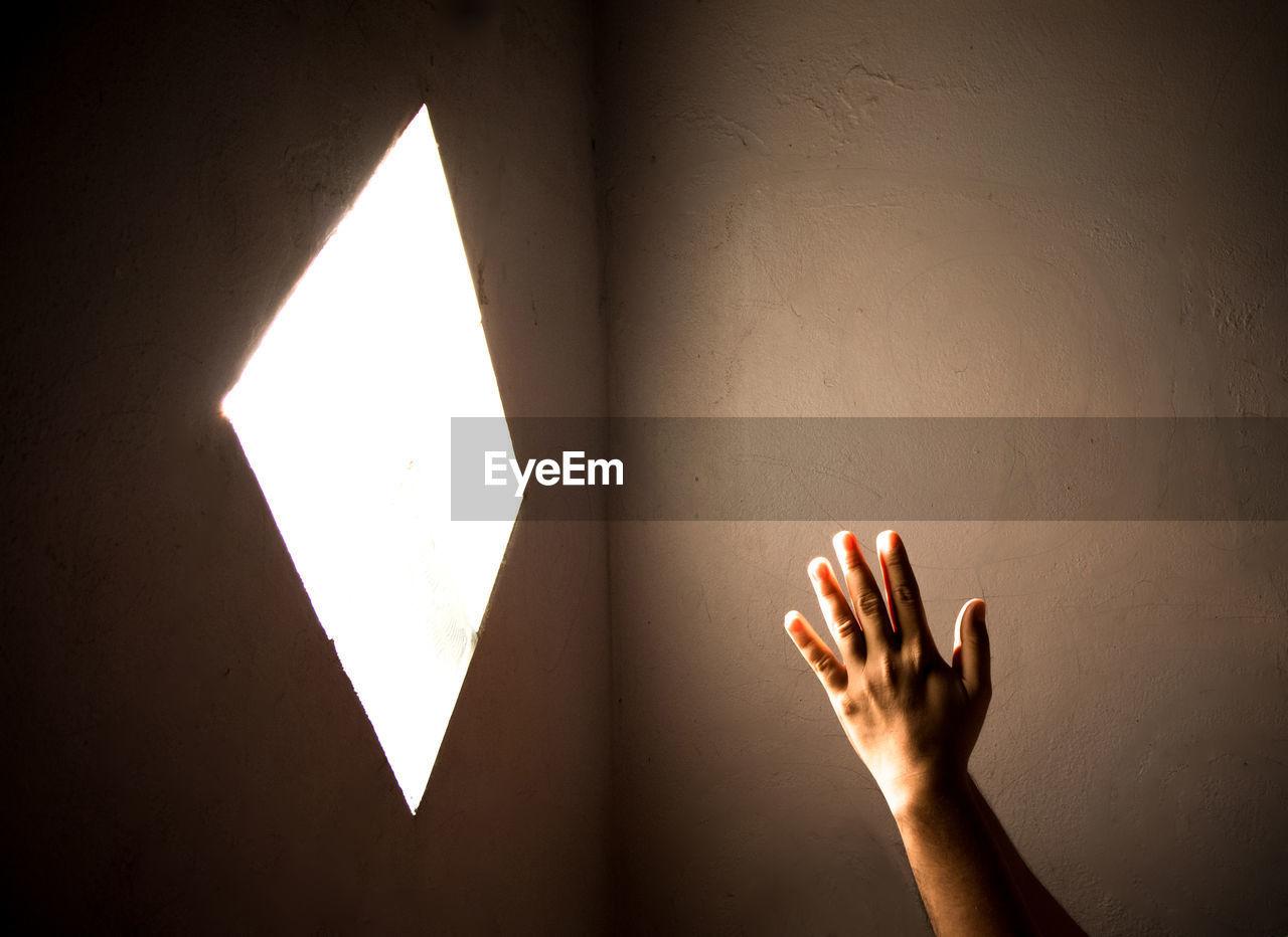 Close-up of praying hand holding illuminated light