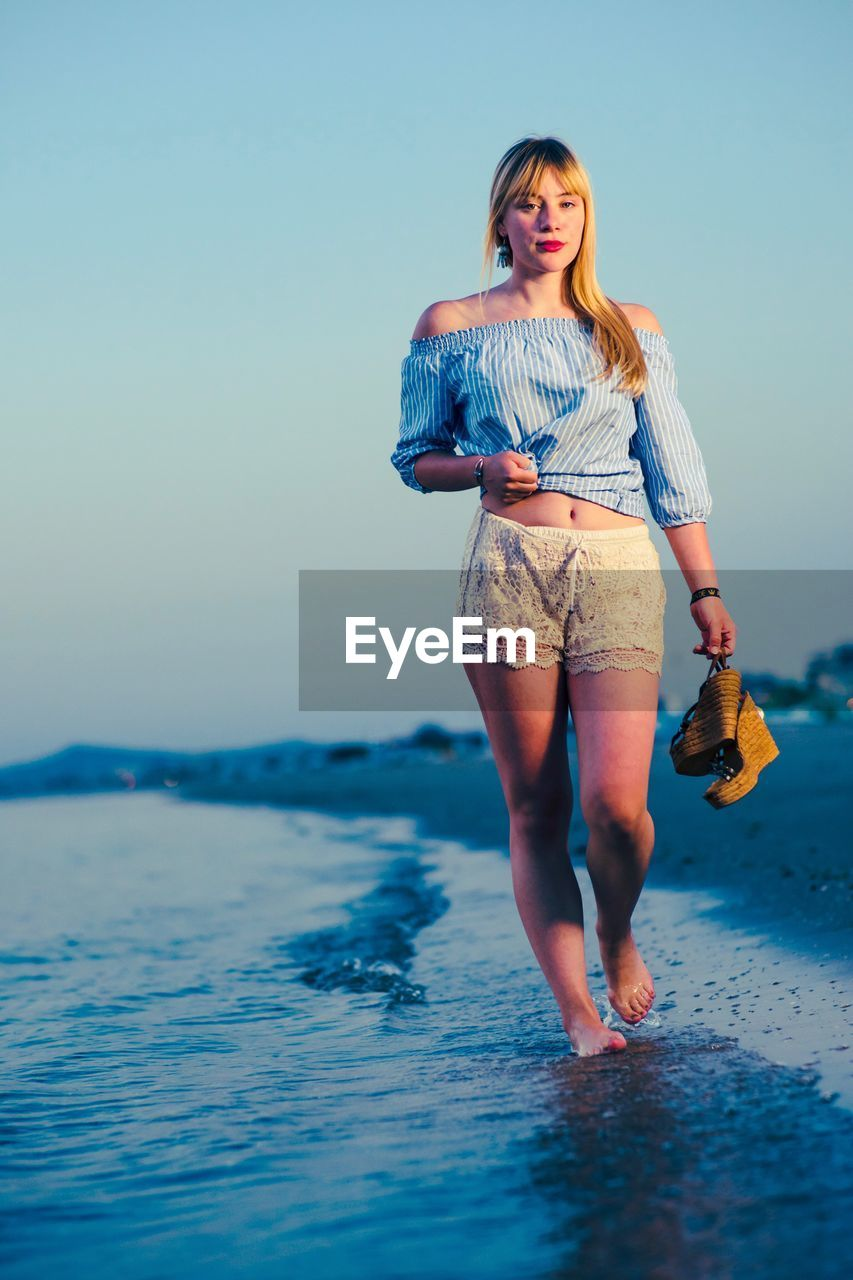 Portrait Of Beautiful Woman Holding High Heels While Walking At Beach Against Clear Sky During Sunset