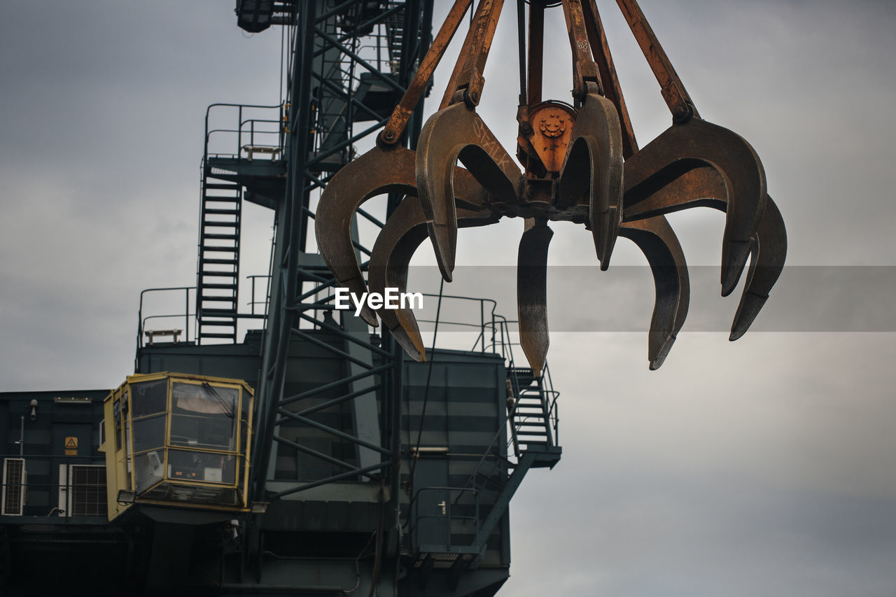 Low angle view of scrap metal and crane against sky