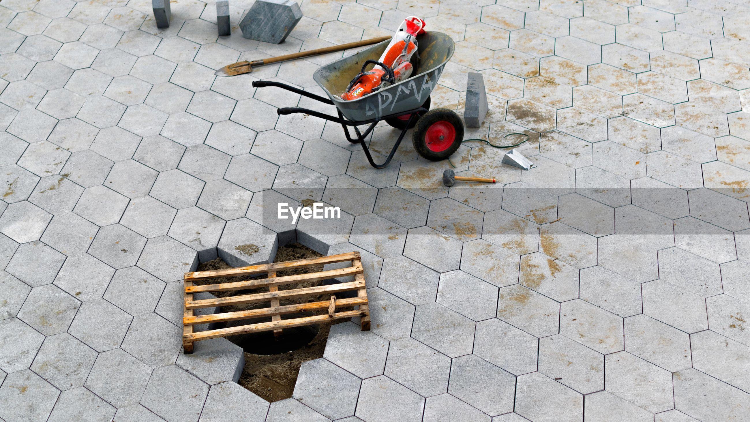 High angle view of wheelbarrow and work tools on street