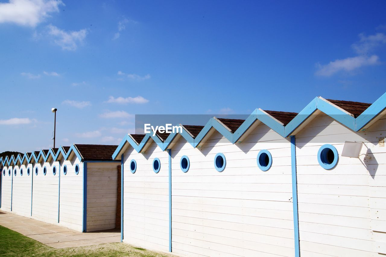 built structure, architecture, building exterior, sky, cloud - sky, day, beach hut, blue, nature, side by side, no people, building, sunlight, hut, wood - material, in a row, outdoors, house, pattern, white color