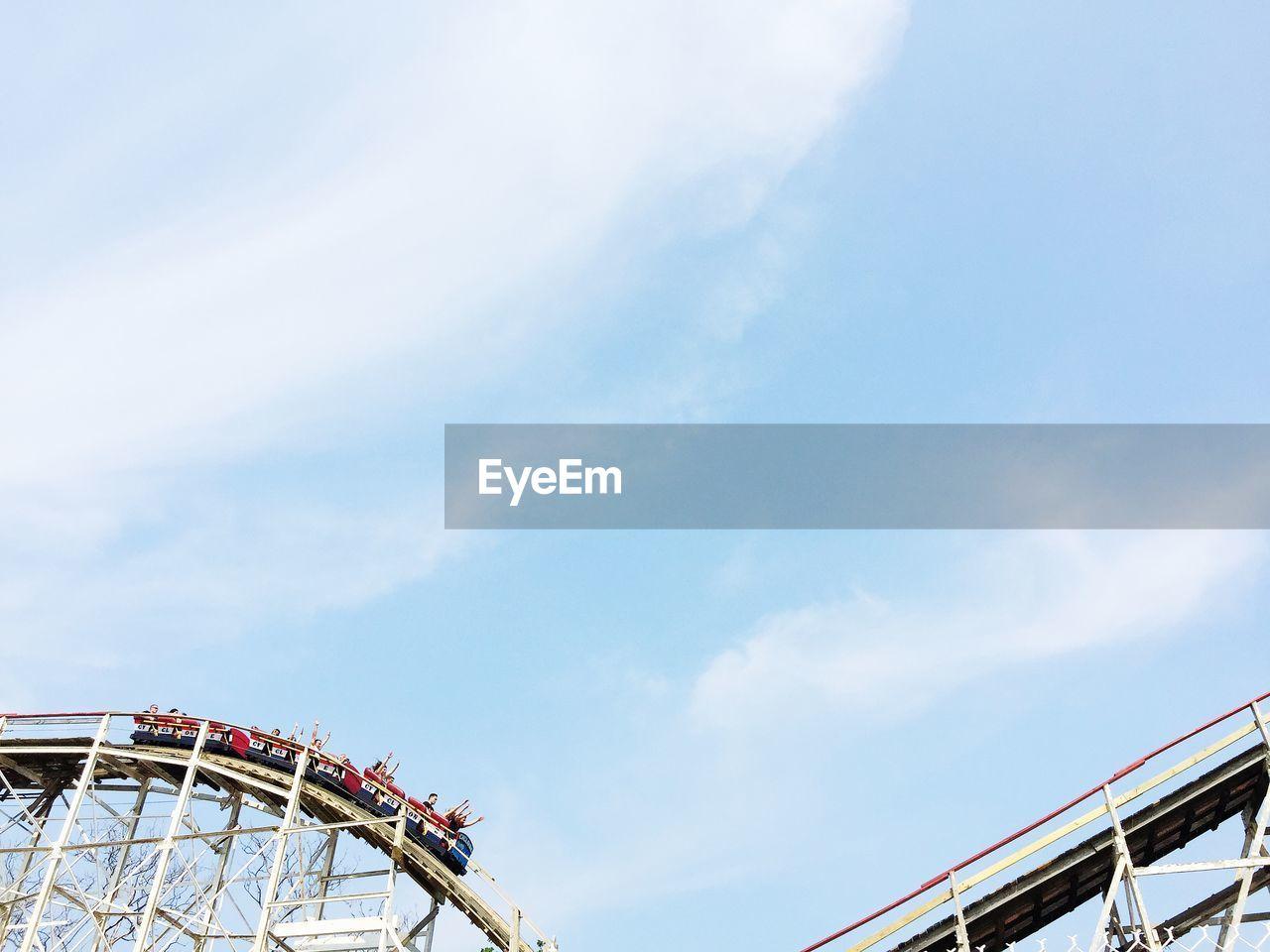People On Rollercoaster Against Sky