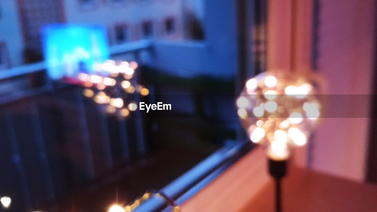 illuminated, lighting equipment, night, glowing, architecture, no people, focus on foreground, building exterior, defocused, built structure, light - natural phenomenon, close-up, decoration, city, motion, celebration, selective focus, electricity, blurred motion, light
