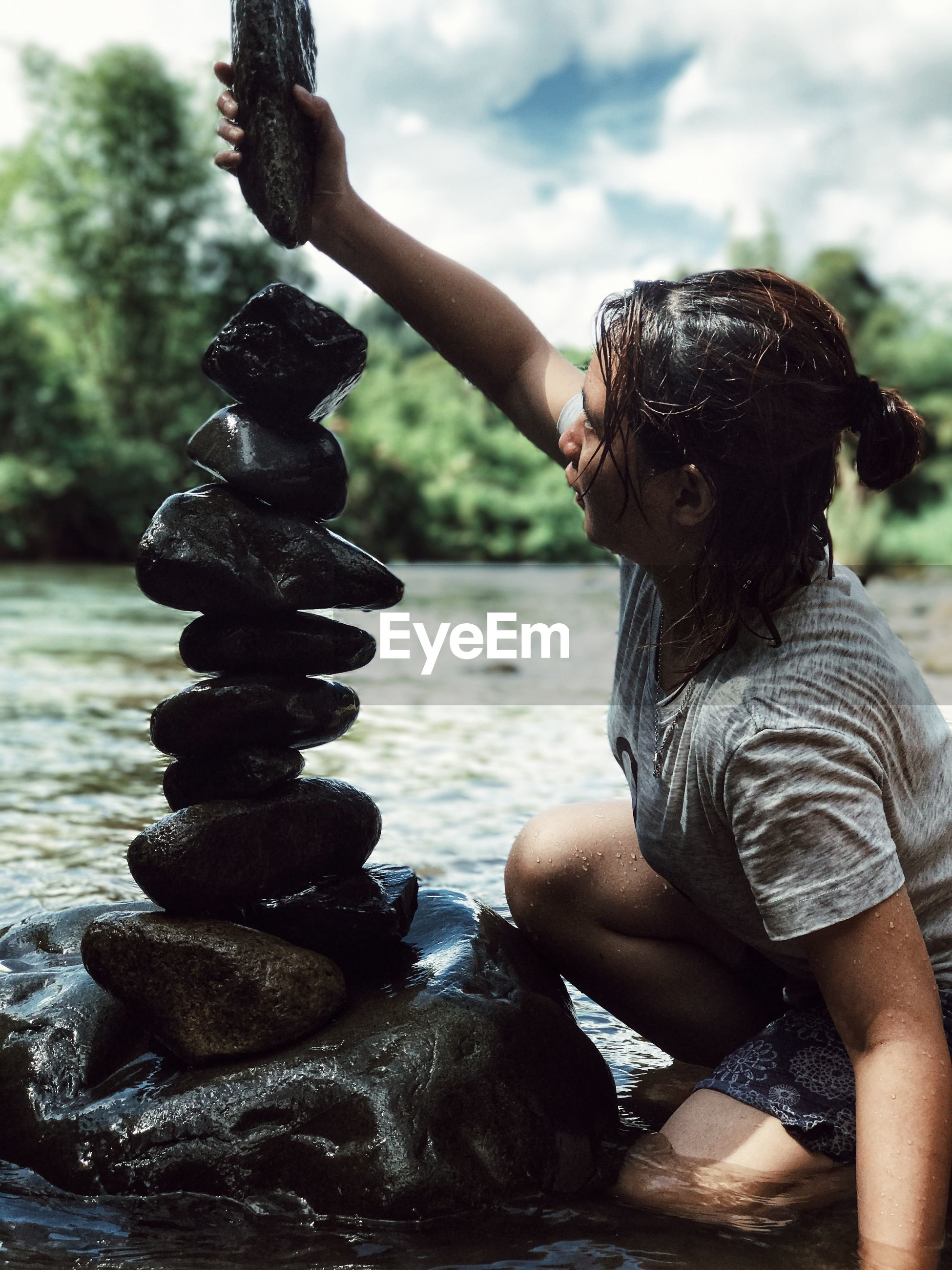 Young woman stacking pebbles by river