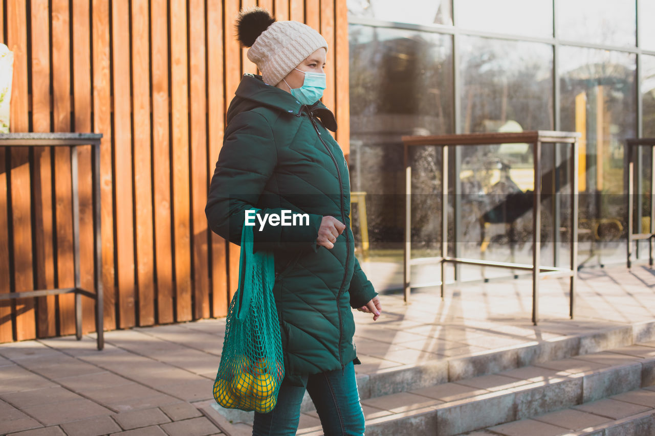 Full length of woman standing on footpath during winter