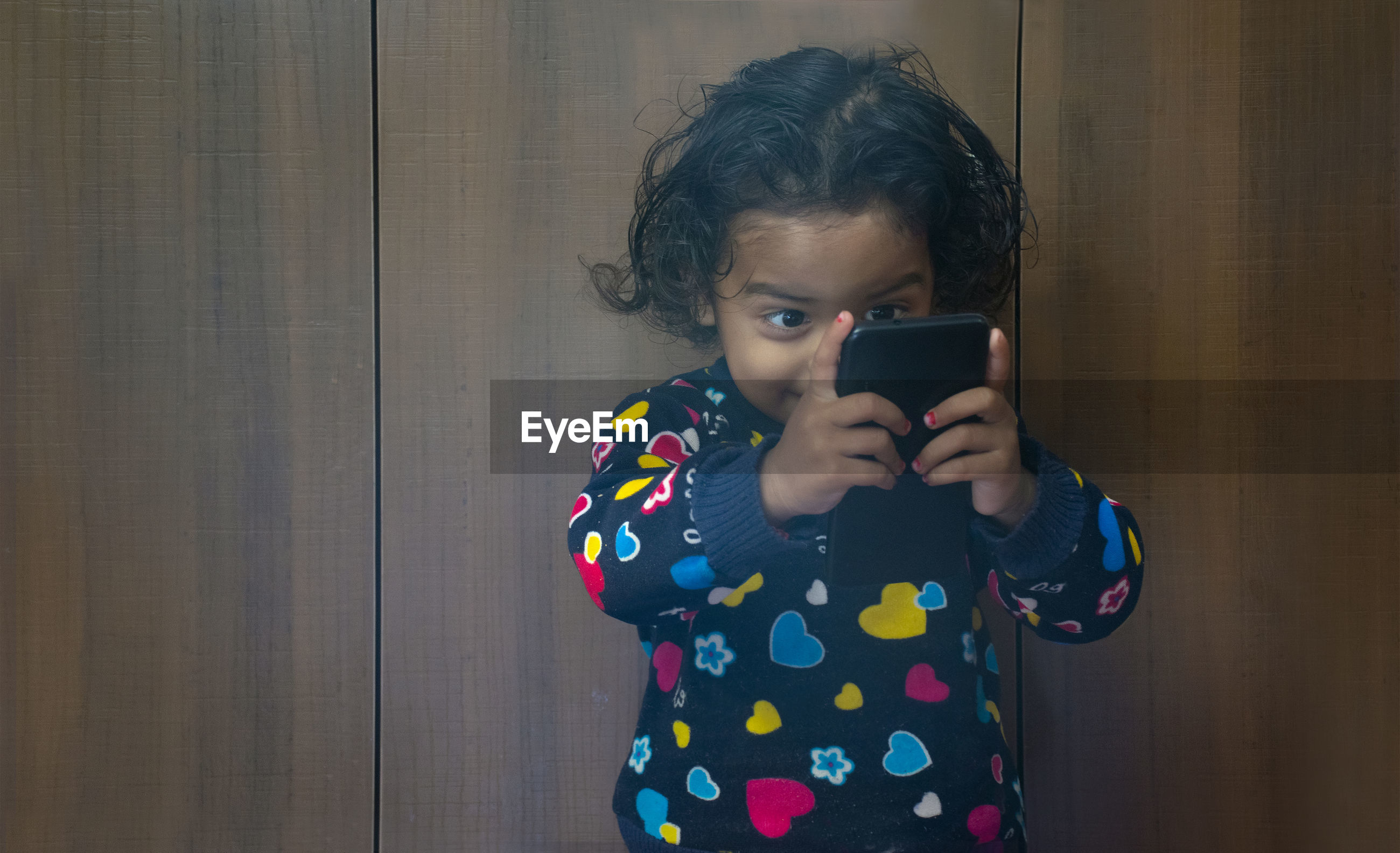 Close-up of girl holding smart phone against closet