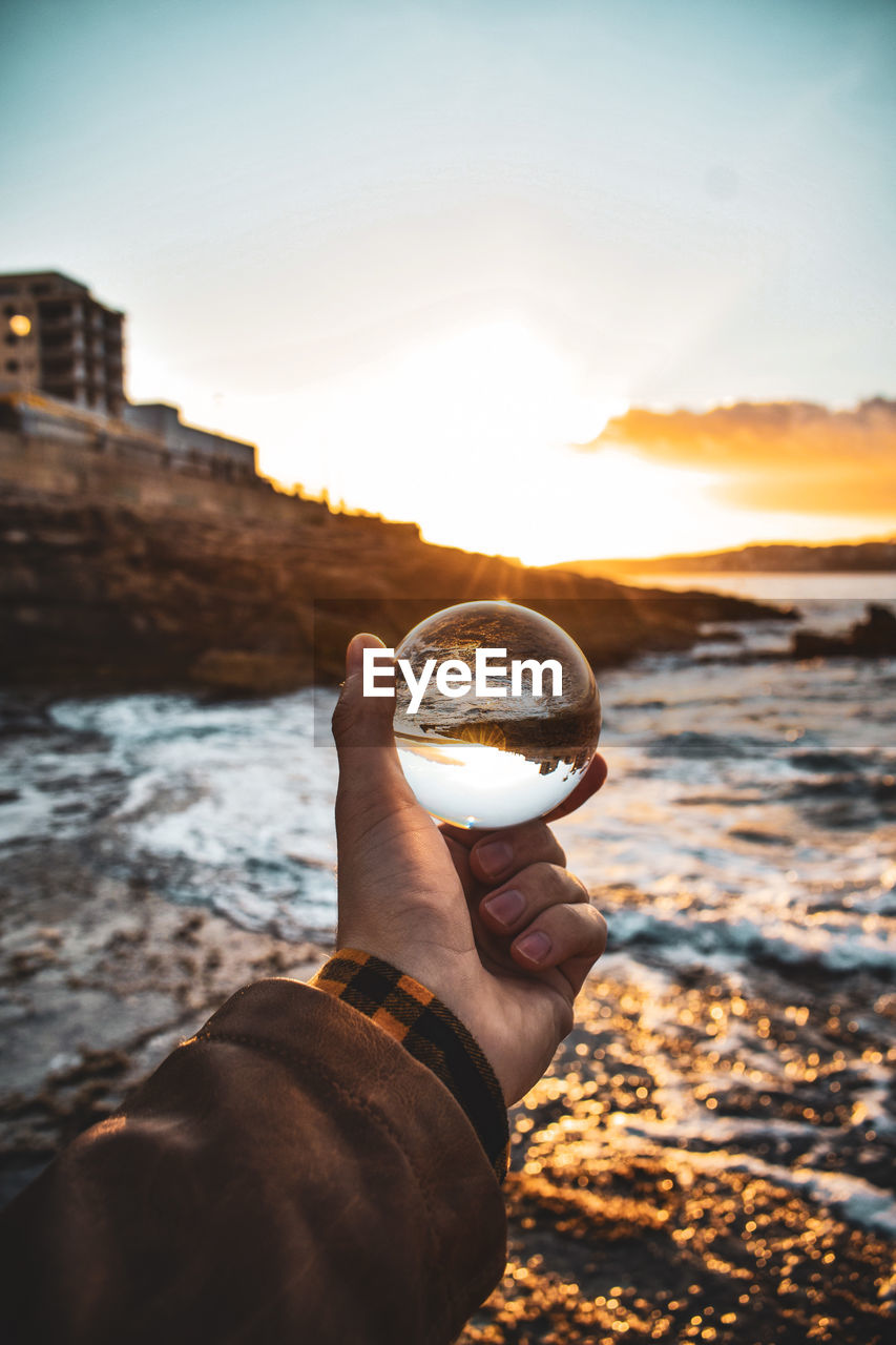 Cropped hand holding crystal ball against sea during sunset
