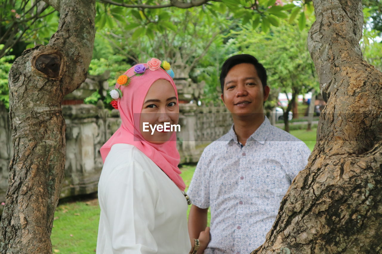 Portrait of smiling couple standing by tree trunks in park