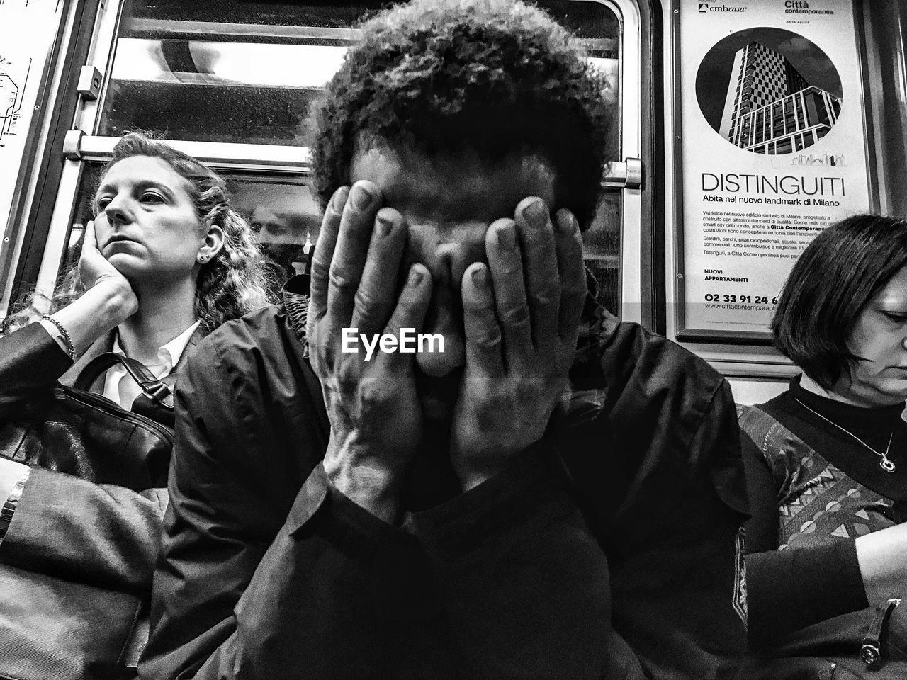 PORTRAIT OF MAN SITTING IN TRAIN