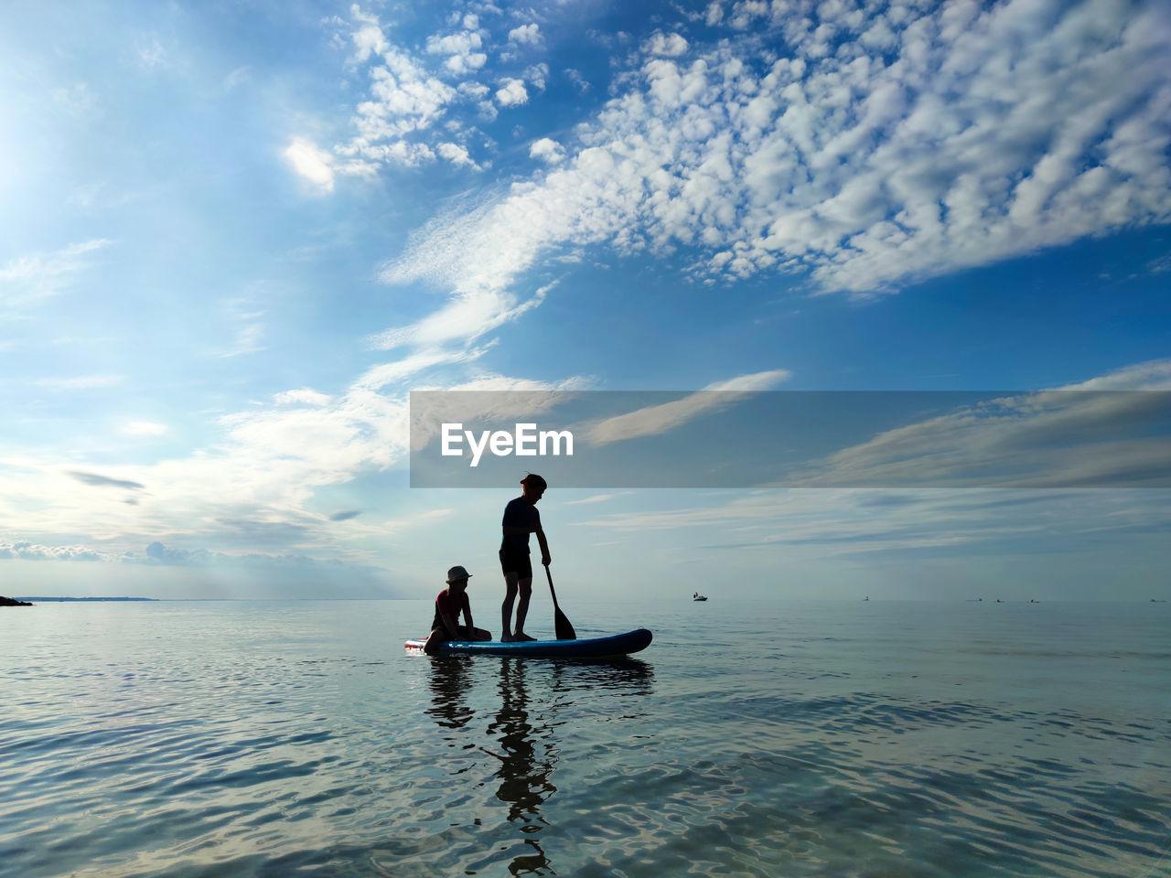 Silhouette siblings paddleboarding on sea against sky