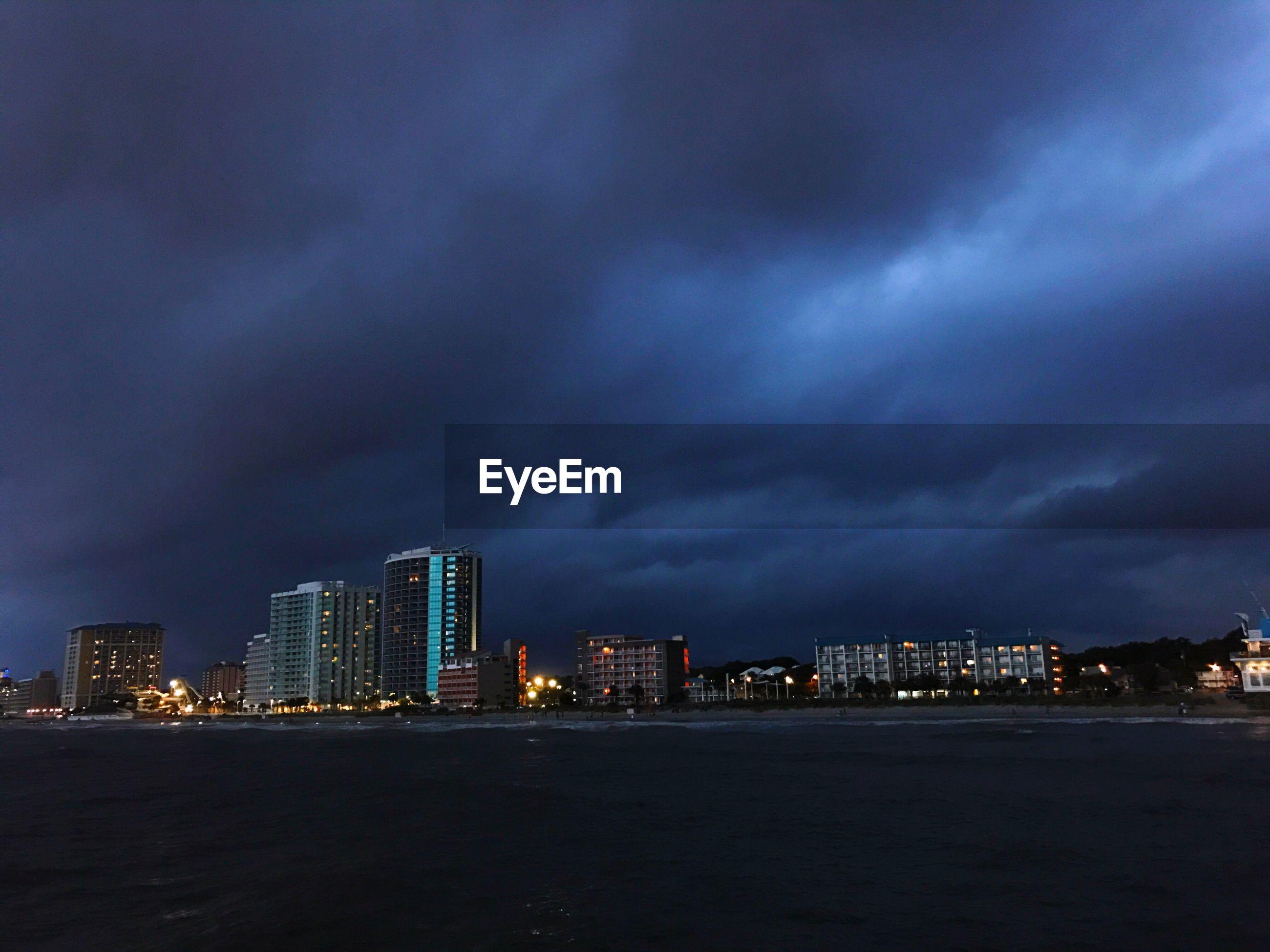 ILLUMINATED CITY AGAINST CLOUDY SKY