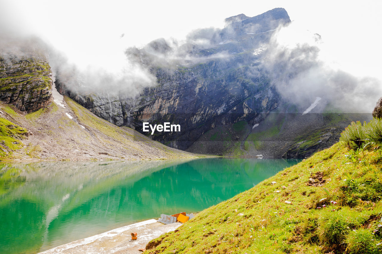 mountain, scenics - nature, beauty in nature, tranquil scene, water, tranquility, lake, nature, non-urban scene, day, mountain range, sky, idyllic, environment, cloud - sky, plant, no people, landscape, green color, outdoors, mountain peak