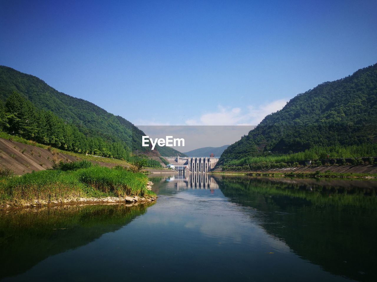 Scenic View Of River By Mountains Against Clear Blue Sky
