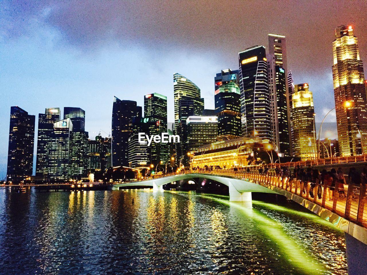 Illuminated cityscape by marina against sky