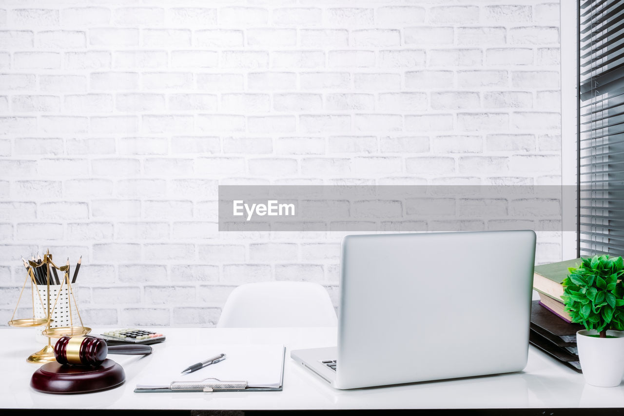 laptop, table, technology, computer, wireless technology, indoors, brick wall, office, brick, no people, communication, business, wall, connection, wall - building feature, copy space, furniture, pen, white color, day, glass