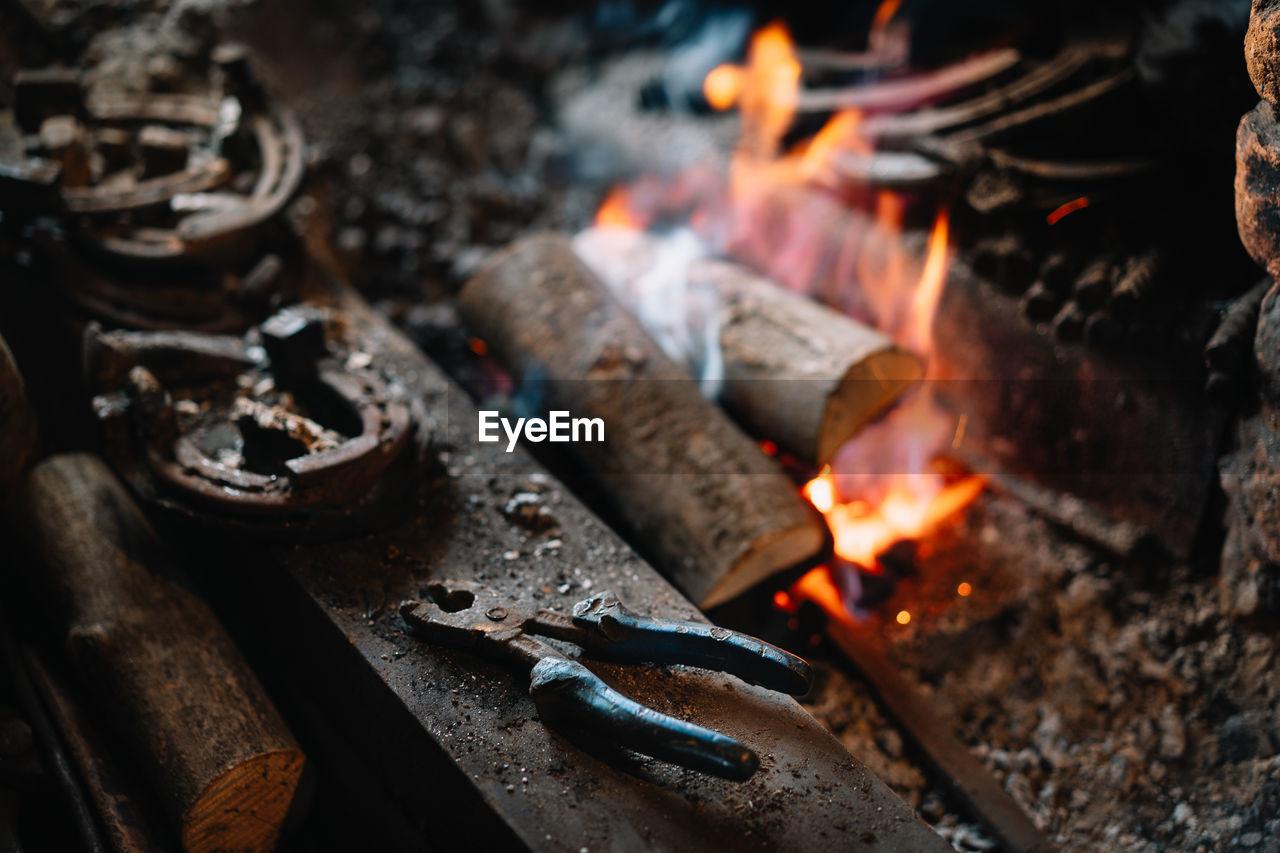 High angle view of blacksmith hand tool by bonfire